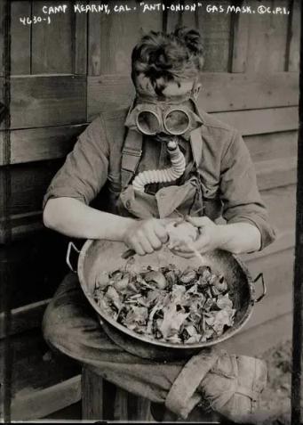 Американский солдат в тренировочном лагере чистит лук в противогазе, США, 1918 год