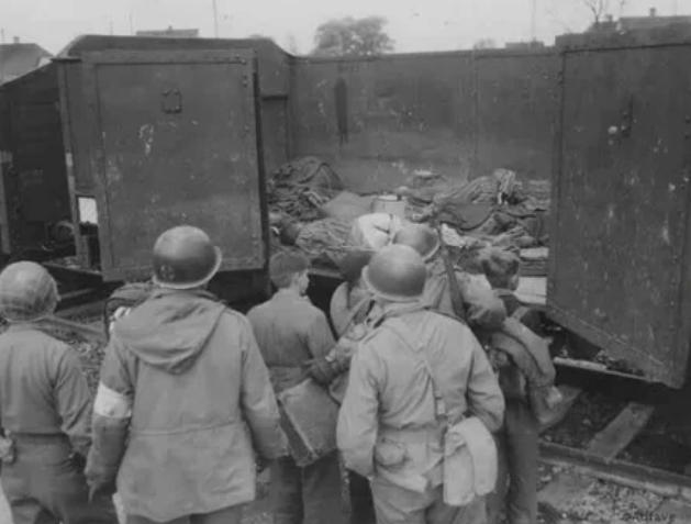 Американские солдаты показывают подросткам из «Гитлерюгенда» тела узников в вагоне, в концлагере Дахау, 1945 год