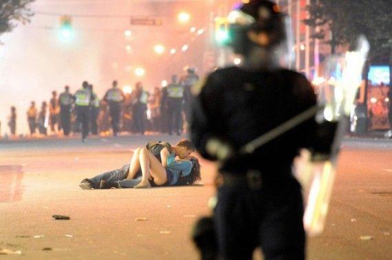 девушка и парень целуются посреди бунта
