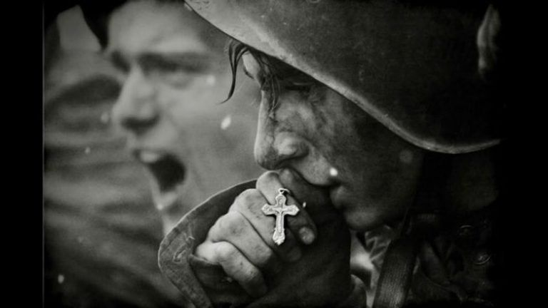 Современное, постановочное фото с целующим крестик советским солдатом