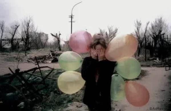 Девочка закрывает глаза от фотографа в центре разрушенного города Грозный, Чечня март 2002 года