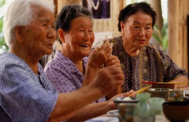 Пожилые люди наслаждаются трапезой в тесном кругу друзей