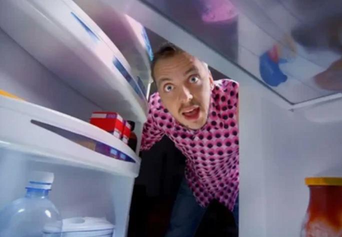 парень заглядывает в холодильник