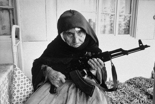 Старая женщина с оружием в руках защищает свой дом