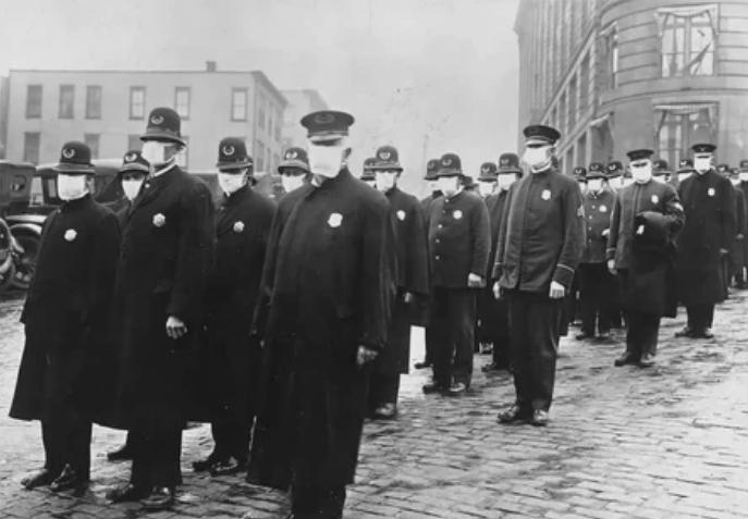Полицейские стоят на улице в Сиэтле, Вашингтон, в защитных масках, изготовленных сиэтлийским отделением Красного Креста, во время эпидемии гриппа в 1918 году