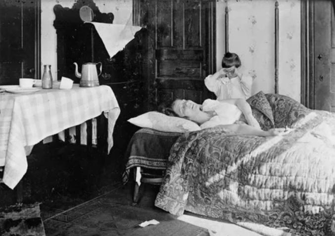 Девочка стоит рядом с сестрой, которая лежит в постели, ноябрь 1918 года